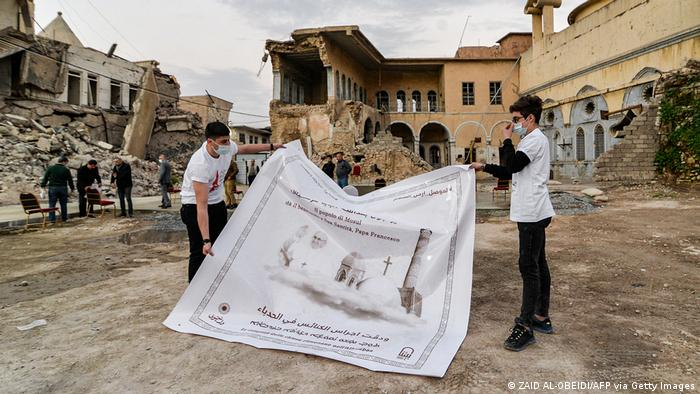 Youths unfurl a poster welcoming Pope Francis in the ruins of the Syriac Catholic Church of the Immaculate Conception in Mosul.