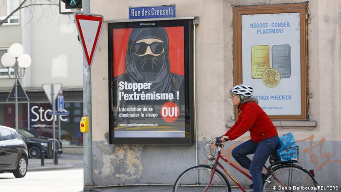 Mulher de bicicleta passa por cartaz de campanha pela proibição da burca