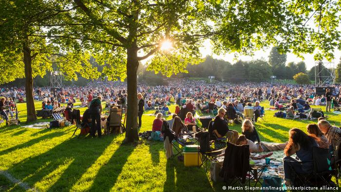 Menschen sitzen bei Sonnenschein mit Decken und Stühlen eng beieinander auf einer Wieser