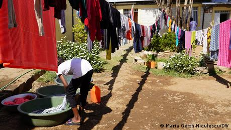 A young lady washes and hangs clothes outside.