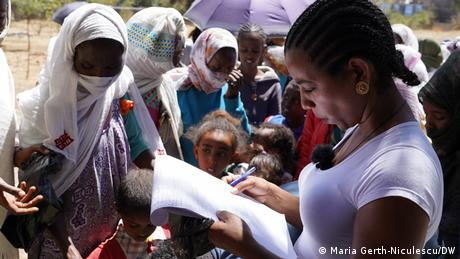 A woman looks at a notebook and pen as a crowd gathers around.
