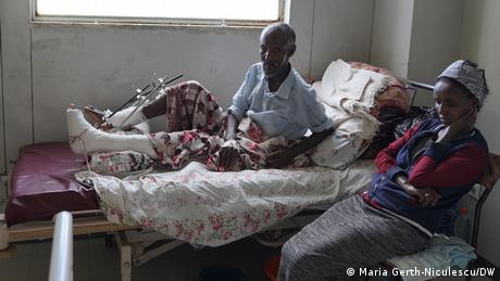 A man with bandaged legs lays on a hospital bed as a woman sits by.