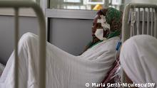 A woman lies on a hospital bed.