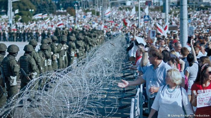 Film still 'Courage': police guards on one side of barbed wire and people with Belarus flags on the other side.