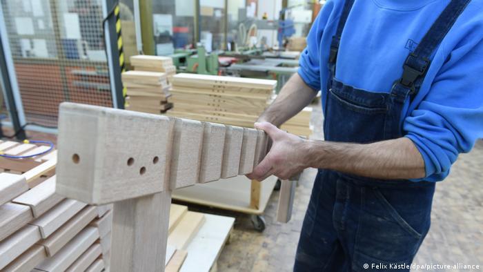 Заключенный работает с древесиной в столярной мастерской