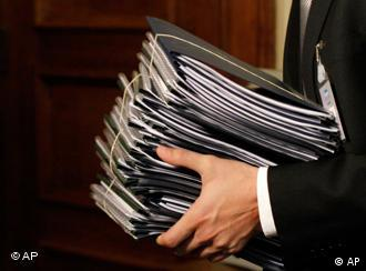 Man carries a file of folders relating to Greece's budget cuts