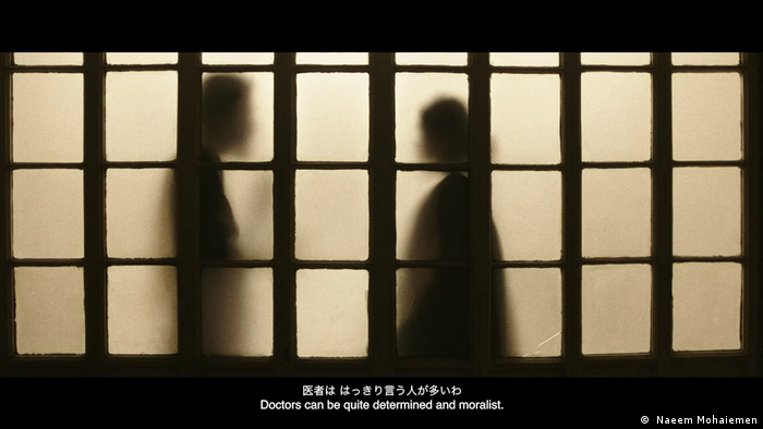 A film still from Jole Dobe Na showing shadows of two persons behind a screen