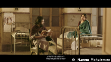 A film still showing a man reading out from a book to a woman at a hospital