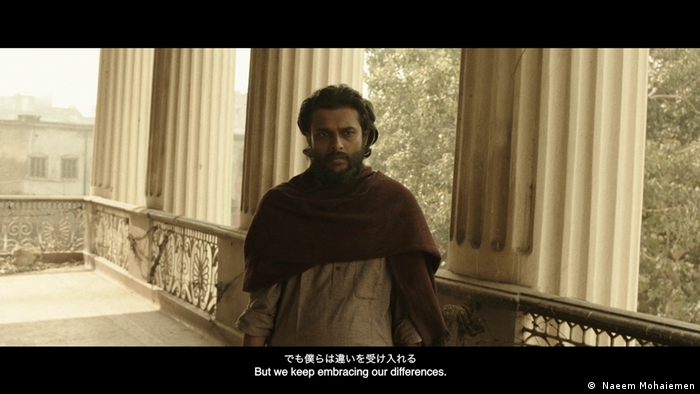 A film still showing a man on a balcony supported by huge pillars