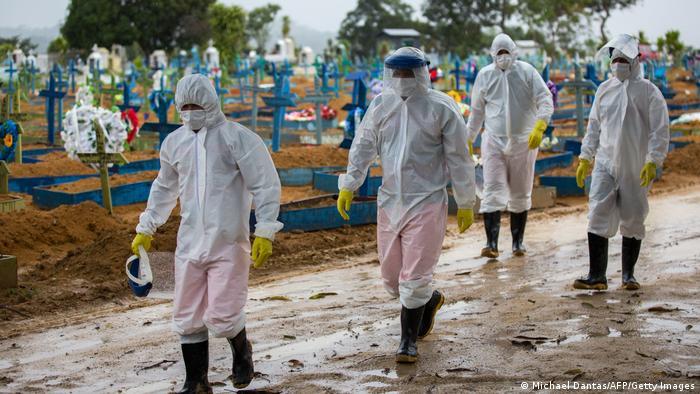 Trabajadores en un cementerio de Manaos, Brasil, con trajes protectores contra el coronavirus.