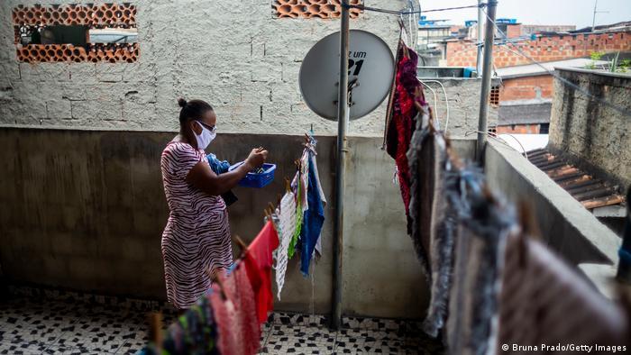 Mulher pendura roupas no Complexo da Maré, no Rio