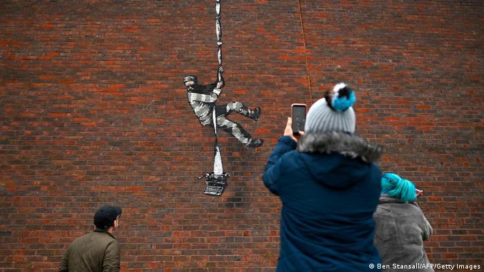 Menschen fotografieren eine Backsteinmauer, darauf zu sehen ist ein Graffito mit einem Ausbrecher, der sich an aneinandergeknüpften Bettlaken abseilt, am Ende der Laken hängt eine Schreibmaschine