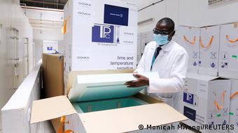 Кенийский медик рядом с коробкой вакцин AstraZeneca, поступивших по программе COVAX
