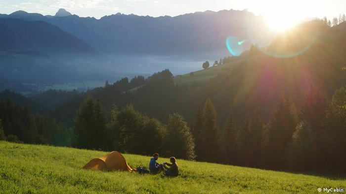 A couple camping on a mountain meadow sitting in front of their tent