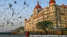 "*** Dieses Bild ist fertig zugeschnitten als Social Media Snack (für Facebook, Twitter, Instagram) im Tableau zu finden: Fach ""Images"" —> Weltspiegel/Bilder des Tages *** 04.03.21 *** TOPSHOT - A couple poses for photographs in front of the Taj Mahal hotel in Mumbai on March 4, 2021. (Photo by Punit PARANJPE / AFP) (Photo by PUNIT PARANJPE/AFP via Getty Images)"