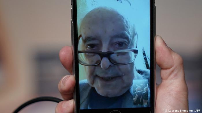 Jean-Luc Godard mit tief auf der Nase sitzender Brille gibt via Handy ein Interview.