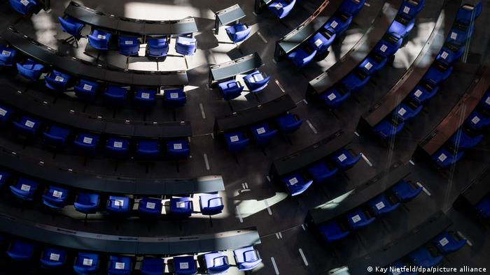 Light falls on the empty seats in the Bundestag
