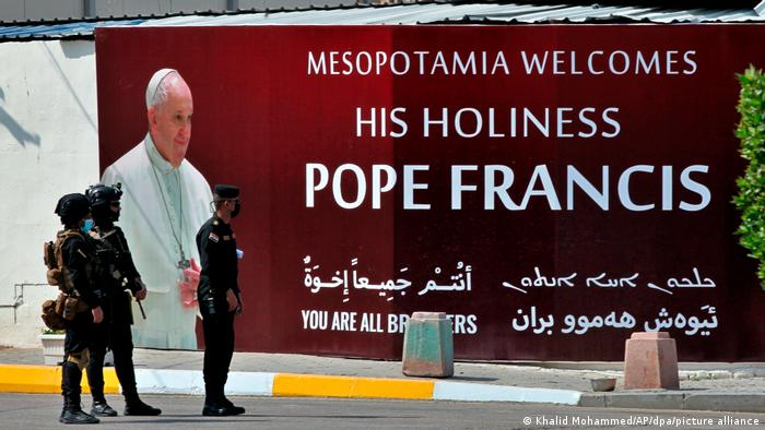 Iraqi security forces standing in front of a poster with the words: 'Mesopotamia welcomes His Holiness Pope Francis.' and 'We are all brothers'