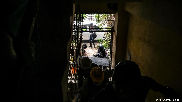 La policía persigue a un grupo de manifestantes por el pasillo de un edificio. Yangon