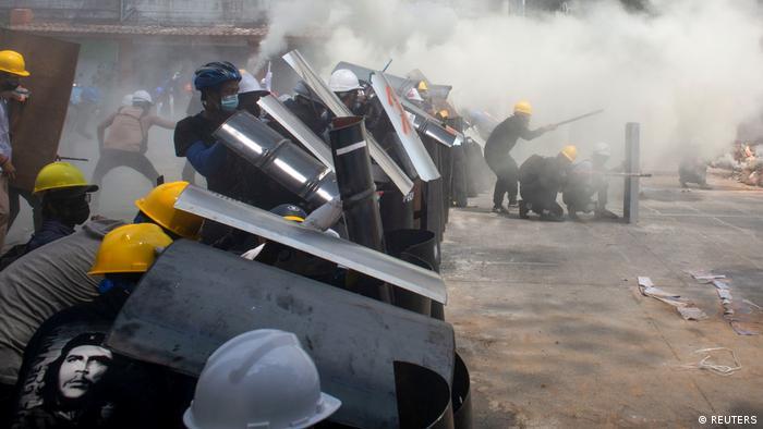 Jóvenes manifestantes con escudos protectores hechos por ellos mismos y policías se enfrentan en las calles de las ciudades.Yangon