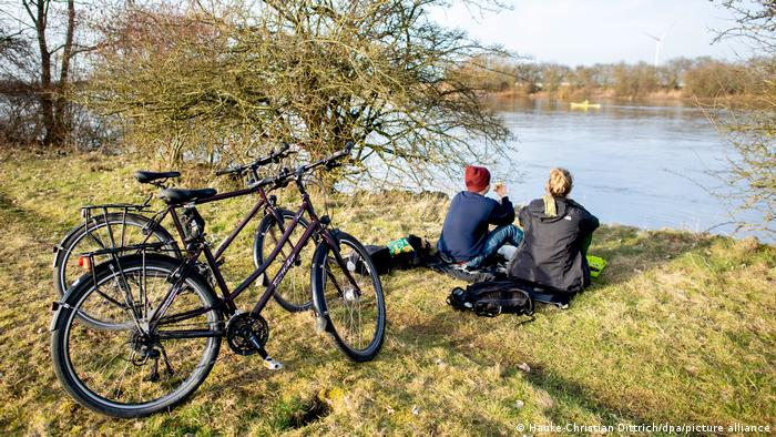 A couple sitting on the banks of a river in front of their bicycles in Germany