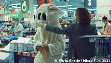 A still from 'Bad Luck Banging or Loony Porn': A masked person touching the nose of a person dressed as a rabbit