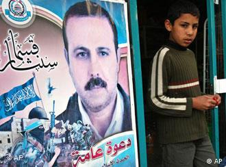 A Palestinian youth walks out of a store covered with posters of assassinated Mahmud al-Mabhuh