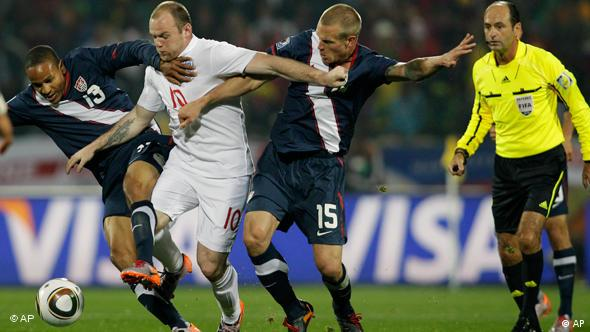 England's Wayne Rooney, second left, is tackled by United States' Ricardo Clark, left, and United States' Jay DeMerit, second from right, during the World Cup group C soccer match between England and the United States at Royal Bafokeng Stadium in Rustenburg, South Africa, Saturday, June 12, 2010.