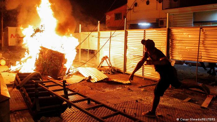 A demonstrator reacts near a fire during a protest against the government's pandemic policies in Asuncion, Paraguay