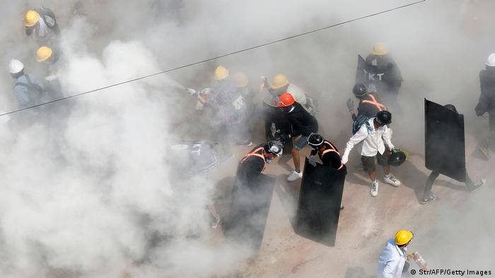 Protesters react as they are engulfed by tear gas fired by police