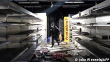 A man walks among the rubbles of a burnt down and looted supermarket in Dakar, Senegal