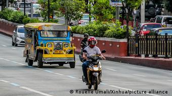 Человек на мотороллере и маршрутное такси-джипни в столице Филиппин - Маниле