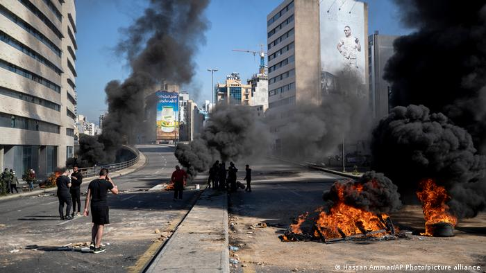 Protesters stand next to burning tires set on fire to block a main road in Beirut, Lebanon