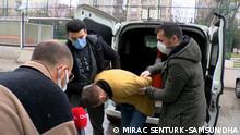 Zwei Polizisten bei der Festnahme des Mannes, ein Journalist beobachtet