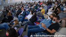 Audience members wear protective face masks during a performance of Israeli musician Ivri Lider at a soccer stadium in Tel Aviv, Friday, March. 5, 2021. All guests were required to show green passport proof of receiving a COVID-19 vaccination or full recovery from the virus. (AP Photo/Oded Balilty)