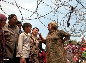 Refugees standing next to barbed wire