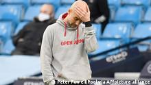Manchester City's head coach Pep Guardiola walks by the touchline during the English Premier League soccer match between Manchester City and Manchester United at the Etihad Stadium in Manchester, England, Sunday, March 7, 2021. (Peter Powell/Pool via AP)