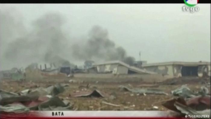Smoke rises from destroyed structures following explosions at a military base