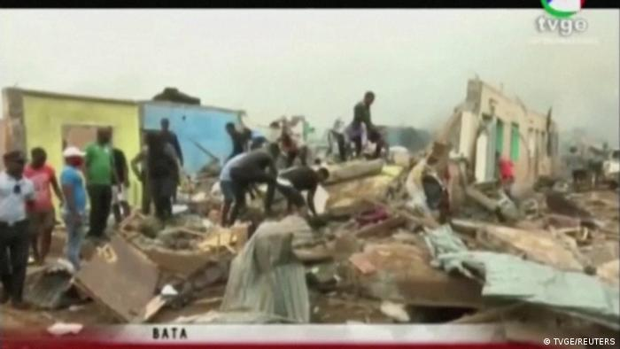 In a screenshot from TVGE, people search through rubble following explosions at a military base