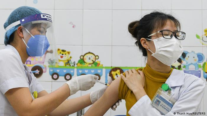 A young healthcare worker receives an AstraZeneca shot in Vietnam, March 2021