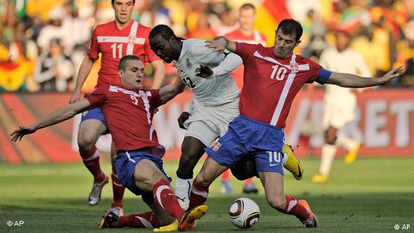 Ghana's Prince Tagoe, center, is caught between Serbia's Nemanja Vidic, left, and Dejan Stankovic, right, during the World Cup group D soccer match between Serbia and Ghana at the Loftus Versfeld Stadium in Pretoria, South Africa, Sunday, June 13, 2010.