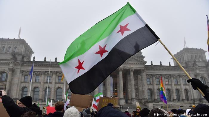 A group of protesters holding a Syrian flag in front of the Reichstag in Berlin