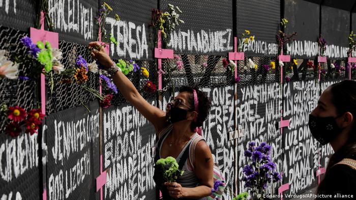 A woman place flowers on a perimeter fence set up in front of the National Palace in preparation for the upcoming International Women's Day demonstration, in Mexico City, Sunday, March 7, 2021.