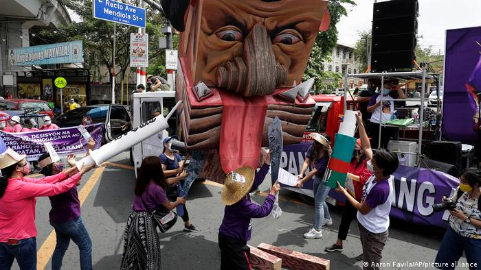 Women activists destroy an effigy of Philippine President Rodrigo Duterte during a rally near the Malacanang presidential palace to mark International Women's Day on Monday March 8, 2021 in Manila, Philippines.