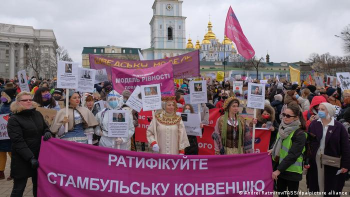 Participants in a women's march the pandemic has a woman's face mark the International Women's Day in Kyiv.