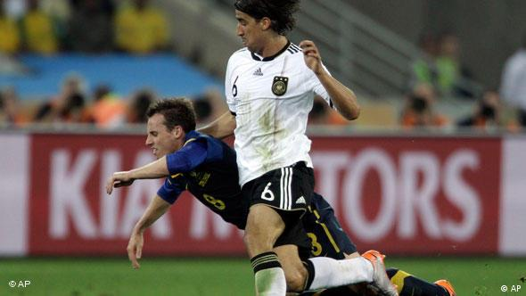 Australia's Luke Wilkshire, left, is challenged by Germany's Sami Khedira during the World Cup group D soccer match between Germany and Australia at the stadium in Durban, South Africa, Sunday, June 13, 2010.