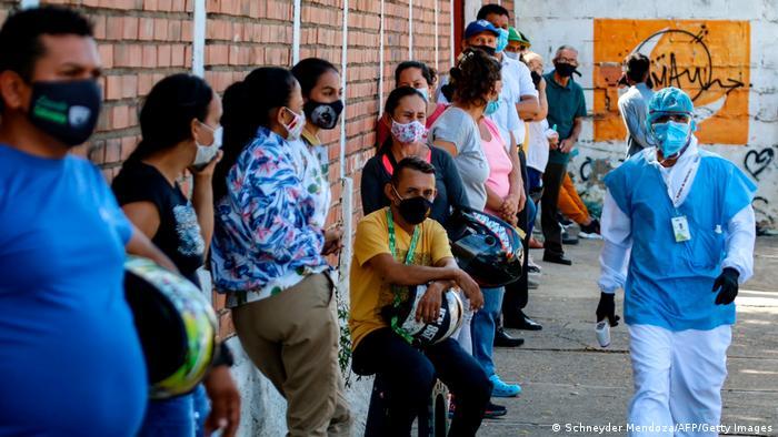 Pessoas com máscaras caseiras aguardam em fila. Profissional da saúde com roupa de proteção caminha.