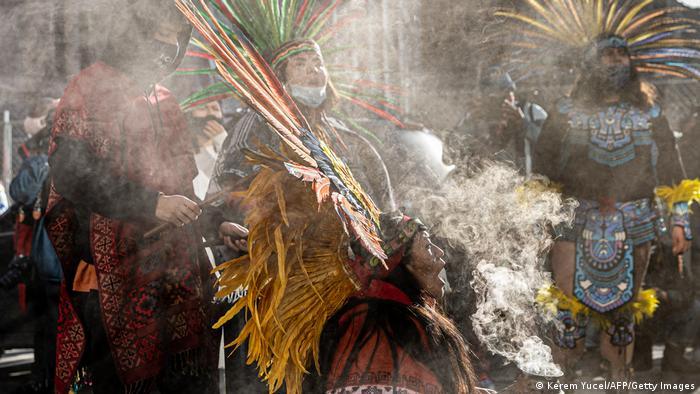 Manifestantes de trajes indígenas em meio a nuvem de fumaça, durante manifestação de rua