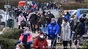 Люди с детьми стоят в очереди в зоопарк Кронберга (федеральная земля Гессен)