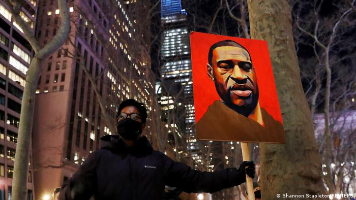 A demonstrator holds up an image of George Floyd at a protest in New York.